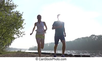 Super slow motion steadicam video of man and girl running on...