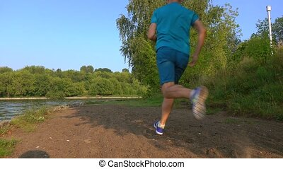Zoom in video of athletic man running by the river, back...