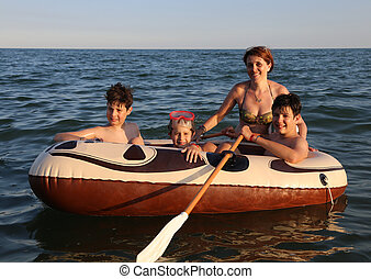 three brothers with mom on the dinghy sailing on the sea in...
