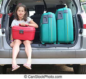 little girl with brown hair long loads the suitcase in the...