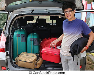 smiling little boy with glasses loaded the trunk of the car...