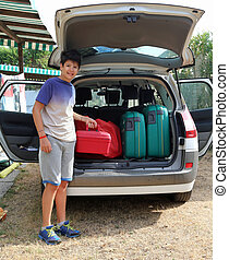 boy helps load the trunk before leaving for a long journey -...