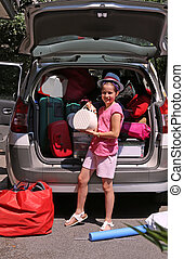 little girl with Hat loads the trunk - nice little girl with...