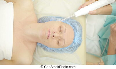 Receiving electric darsonval facial massage procedure....