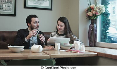 Business partners during lunch at cafe, with documents - Two...