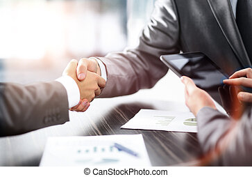 Business partners shaking hands at the table