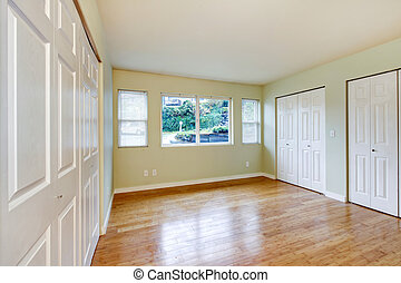 Empty room interior with hardwood floor and three closets.