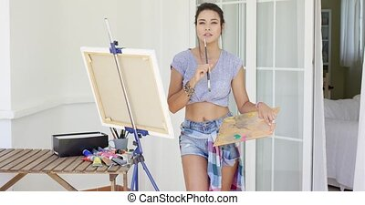 Sexy attractive young female artist standing working on a...