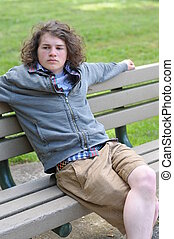 Young adult relaxes on bench - Young white Caucasian...