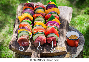 Fresh vegetables and red beef with herbs on grill