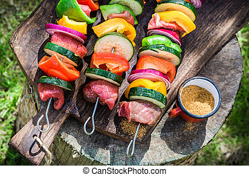 Roasting fresh vegetables and meat with herbs in garden