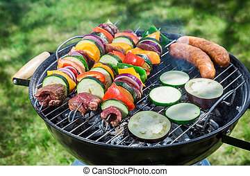 Roasting fresh vegetables and red beef with herbs in garden