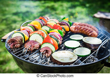 Roasting fresh vegetables and red beef with spices in garden
