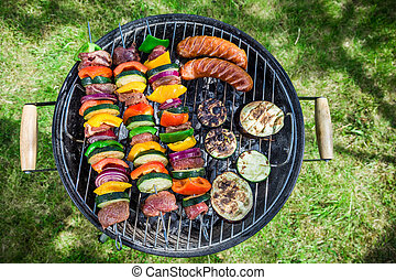 Grilling fresh vegetables and meat with herbs in garden