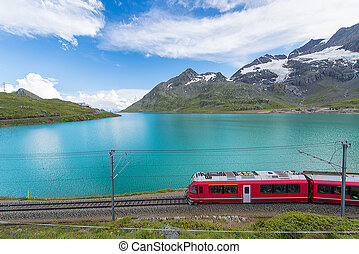 Red train in the high mountains of the Swiss Alps passes near a lake