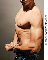 Muscular man flexing his bicep - Young attractive man...