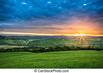 Green fields in the valley at sunset, Tuscany, Italy