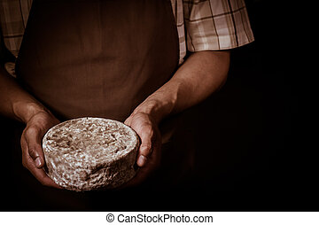 French tomme cheese in the hands of a cheesemaker, Studio...