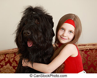 Girl hugging a dog - Gentle little girl, with long brown...