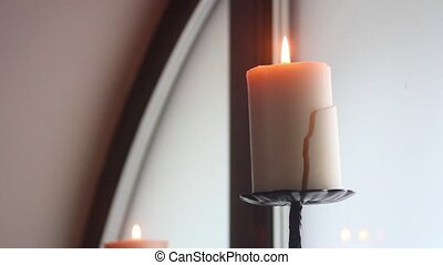 cracked candle in a candlestick - Burning candle on a...