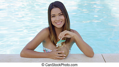 Pretty young woman relaxing in a resort pool - Pretty young...