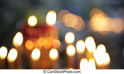 Many wax yellow candles brightly burn in church. They are...