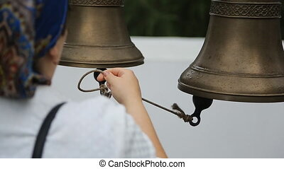 Woman rings in temple bells pulling rope that she keeps in...