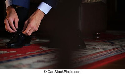 Bridegroom ties laces on his black patent shoes. He prepares...