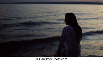 girl sitting on the beach at night