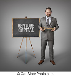 Venture Capital text on blackboard with businessman and key
