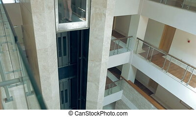 A female is standing in glass moving lift - A female is...