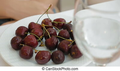 Bright red ripe sweet cherries on a white plate - Bright red...