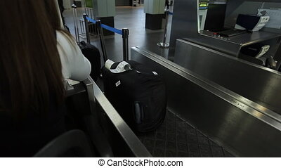 Airport female worker is putting baggage tag on bag. Sitting...
