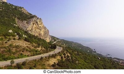 A cars driving along the mountain road on the sea coast.