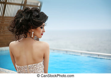 Hairstyle. Beautiful glamour gorgeous woman model with diamond jewelry, makeup red lips. Fashion Girl model posing by swimming pool, Resort.