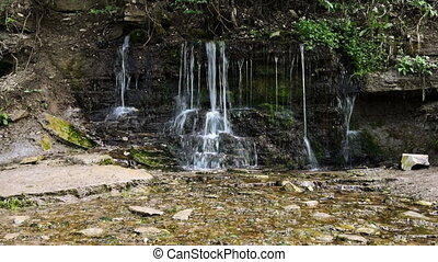 waterfall of spring sources, water flows from a stone wall