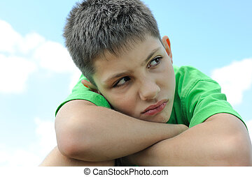Upset boy outdoors - Upset boy is sitting outdoor against...