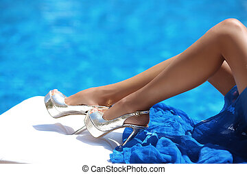close up sexy tanned long legs in high heels lying on deck...