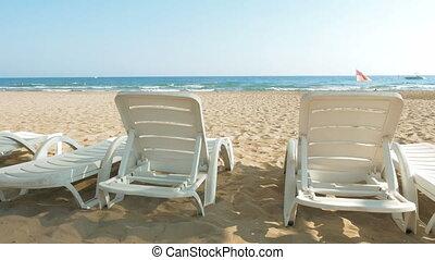 White beach chairs or beds near sea or ocean shore - White...