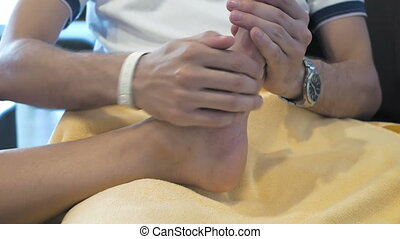 A man is massaging someone's foot - A man is showing a kind...