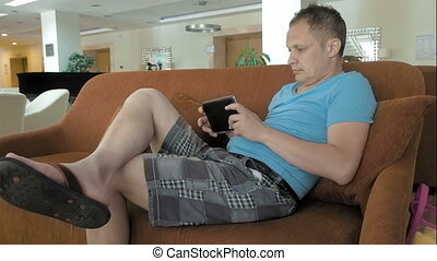 A man is on his mid pad tablet on a couch - A man is shown...