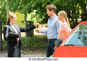 Saleswoman Giving Car Key To Couple - Young Saleswoman...