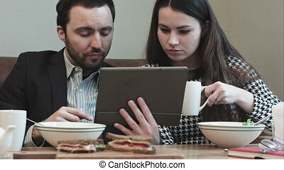 business couple at cafe use tablet while eating