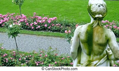 Roses in a large garden In the foreground, a plaster figure...