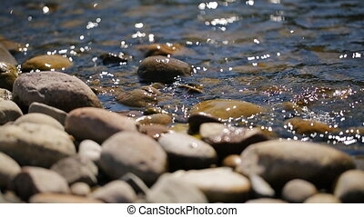 Shallow stony shore washed by glare and spill water on a...