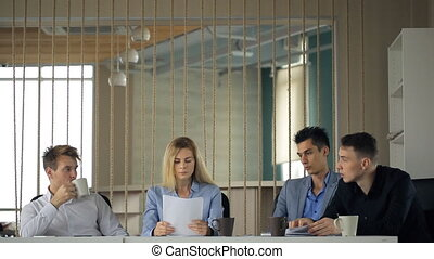Beautiful young woman holding a stack of papers and throws it into air with anger and misunderstanding of his colleagues at table.