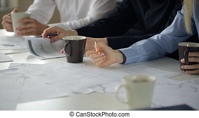 A group of people sitting at confer table in office, woman makes notes with pencil on paper.