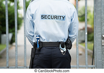 Security Guard Standing In Front Of Gate - Rear View Of A...