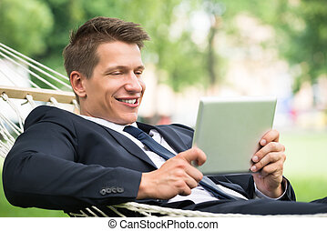 Man Lying In Hammock Using Digital Tablet