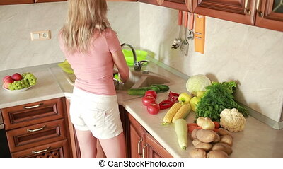 girl washes cucumbers vegetables on the kitchen table...